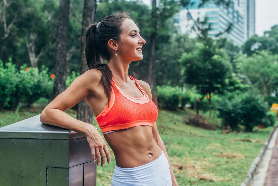 Slim fitness brunette woman with six pack abs wearing pink sport bra standing in city park relaxing after workout looking away from the camera.