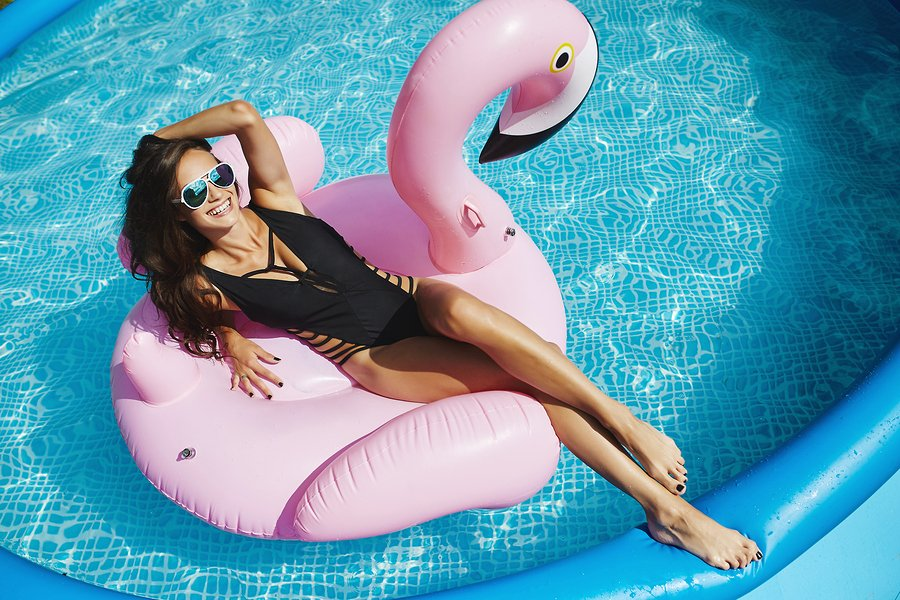 Fashionable, happy and smiling brunette model girl with perfect sexy body in stylish black bikini and glamorous sunglasses, posing on an inflatable pink flamingo at the swimming pool outdoors.