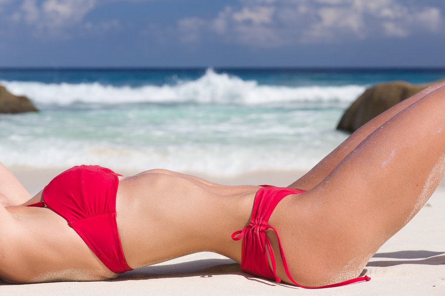 Beautiful and sexy woman body torso in red swimsuit, at tropical sandy beach