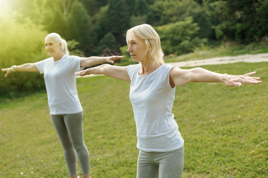 Concentrated elderly ladies stretching out arms while exercising