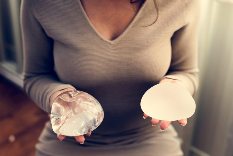 Woman holding silicon bags for breast implant