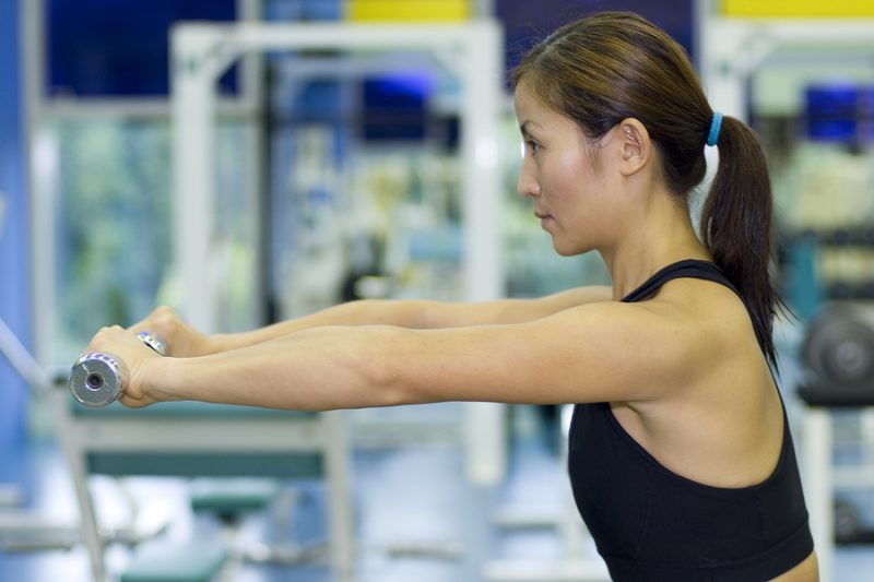 a female fitness instructor demonstrates a dumbbell arm raise in the gym